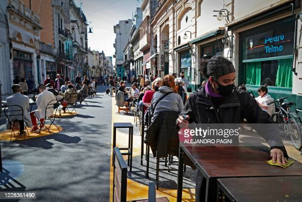 Customers sit at tables placed outside a bar as an employee cleans a table at San Telmo neighborhood, in Buenos Aires, on Septiembre 5 amid the new...