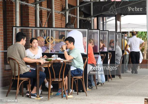 Customers sit at tables separated by dividers outside Peter Luger Steakhouse in Williamsburg as the city continues Phase 4 of re-opening following...