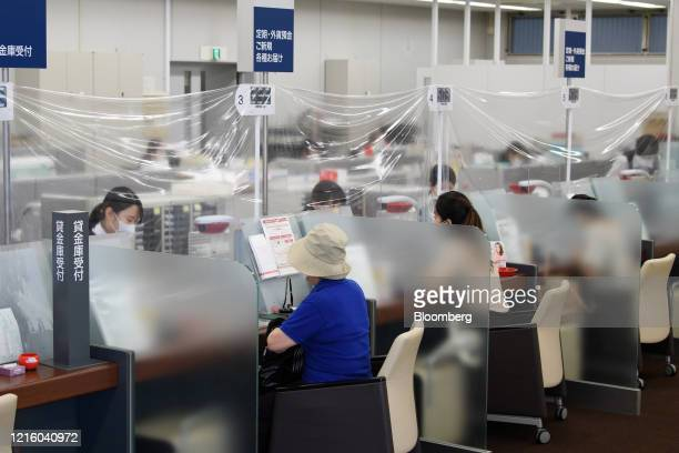 Customers sit at teller stations at a branch of MUFG Bank Ltd., a unit of Mitsubishi UFJ Financial Group Inc. , in Tokyo, Japan, on Friday, May 29,...