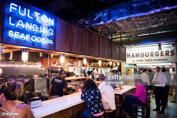Customers sit at the counter of Fulton Landing Seafood Co stand inside DeKalb Market Hall at City Point in the Brooklyn borough of New York US on...