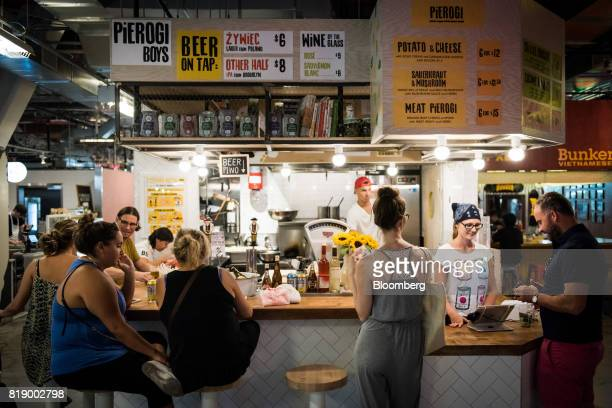 Customers sit at the counter of the Pierogi Boys stand inside DeKalb Market Hall at City Point in the Brooklyn borough of New York US on Tuesday July...