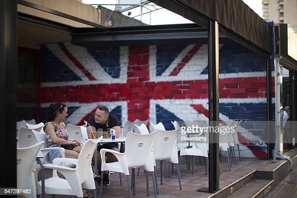 Customers sit at the outdoor terrace of a bar decorated with a British union flag also known as a Union Jack in Benidorm Spain on Monday July 11 2016...