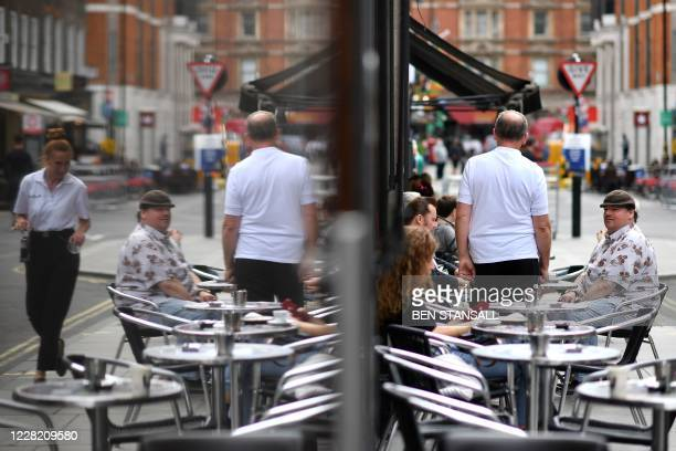Customers sit at the outside tables of a cafe in Soho in London on August 26 as businesses in the busy London area try to keep working despite the...