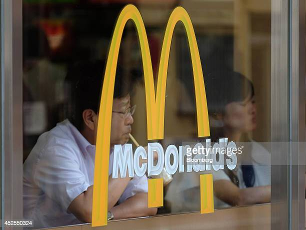 Customers sit behind a logo at a McDonald's restaurant operated by McDonald's Holdings Co Japan Ltd in Tokyo Japan on Wednesday July 23 2014 Japan...