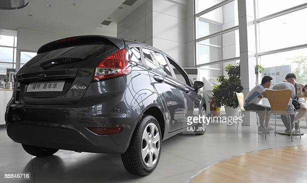 Customers sit beside a new Ford car on display at a dealership in Beijing on July 6 2009 US auto giant Ford Motor Co said on July 6 that sales in...
