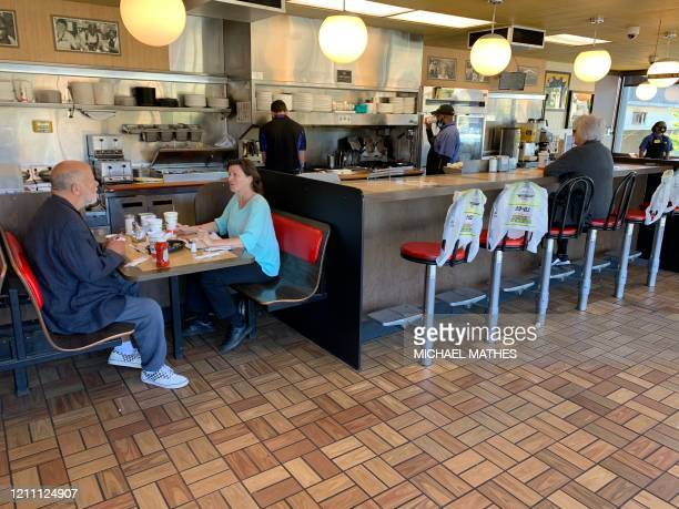 Customers sit for breakfast at a Waffle House in Atlanta as the US state of Georgia relaxed restrictions on April 27 2020 on restaurants to allow for...