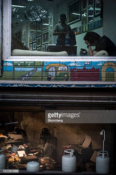 Customers sit in a cafe top while employees work in the basement of a design studio in Hauz Khas Village in New Delhi India on Saturday Sept 15 2012...