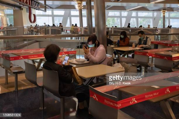 Customers sit in a canteen with taped off seatings to make sure people adhere to social distancing during a coronavirus on March 29 2020 in Hong Kong...