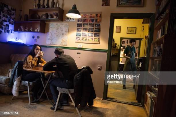Customers sit in a coffee shop in Baku Azerbaijan on Saturday March 17 2018 Azerbaijan's economy barely returned to growth last year increasing 01...