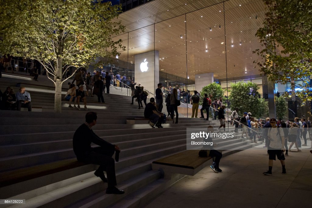 Customers sit in a plaza area outside the new Apple Inc. Michigan Avenue store in Chicago, Illinois, U.S., on Friday, Oct. 20, 2017. The building features exterior walls made entirely of glass with four interior columns supporting a 111-by-98 foot carbon-fiber roof, designed to minimize the boundary between the city and the Chicago River. Photographer: Daniel Acker/Bloomberg via Getty Images