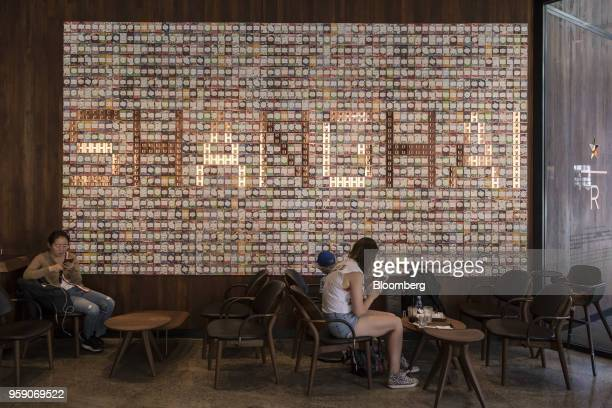 Customers sit in front of a wall display inside the Starbucks Corp Reserve Roastery store in Shanghai China on Friday May 11 2018 Starbucksis laying...