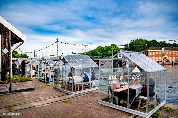 Customers sit in small glasshouses as they enjoy their dinner while keeping a safe distance at the Mediamatic restaurant. The government took a major...