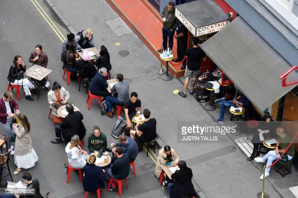 Customers sit in the at tables in the road outside re-opened bars in Soho in London on July 4 as the Soho area embraces pedestrianisation in line...
