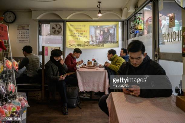 Customers sit in the 'Sky Pizza' restaurant in Seoul on February 13 2020 Locations featured in the South Korea's Oscarwinning Parasite are bracing...