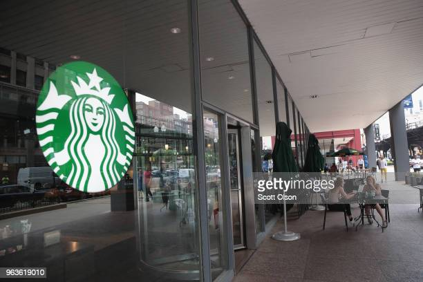 Customers sit on the patio of a Starbucks store after it was closed on May 29 2018 in Chicago Illinois In reaction to a highlypublicized incident in...