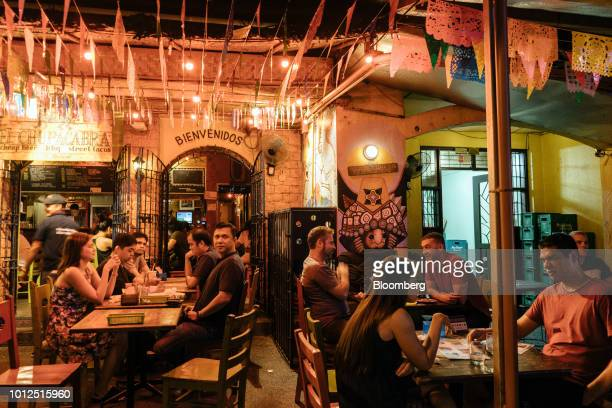 Customers sit outdoors at a bar in the Poblacion area of Makati district in Manila the Philippines on Saturday Aug 4 2018 Consumer prices in the...