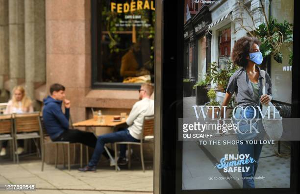 Customers sit outside a bar near a sign promoting postCOVID19 lockdown shopping in Manchester northwest England on August 3 as the Government's Eat...