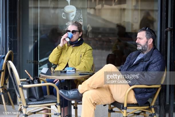 Customers sit outside a Cafe Nero coffee shop in Cardiff, south Wales on October 20 ahead of a short, two-week lockdown due to begin on October 23,...