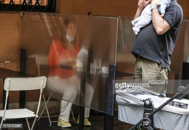 Customers sit outside a cafe with plexiglass panels set to grant safety measures in Rome, Italy, on May 18, 2020. Restaurants, cafes, hairdressers,...