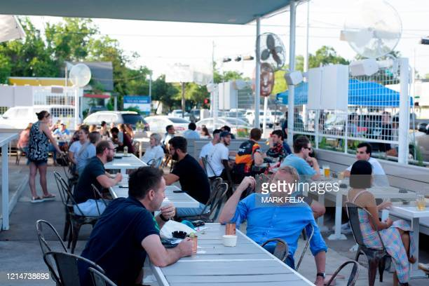 Customers sit outside on the patio at Eight Row Flint in Houston Texas on May 22 amid the novel coronavirus pandemic