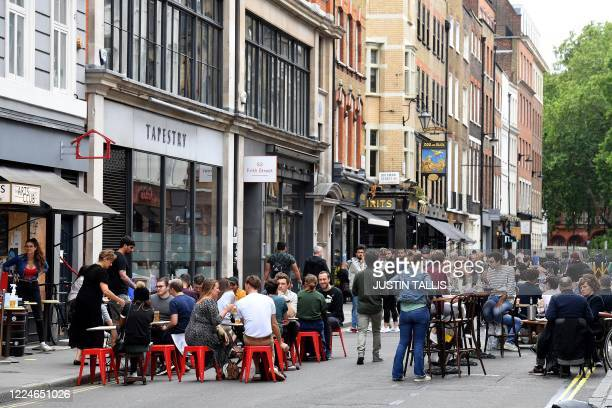 Customers sit outside reopened bars in Soho in London on July 4 as the Soho area embraces pedestrianisation in line with an easing of restrictions...