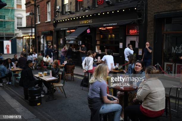 Customers sit outside re-opened bars in Soho in London on July 5 as the Soho area embraces pedestrianisation in line with an easing of restrictions...