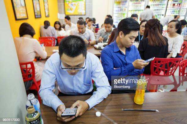 Customers sit using smartphones at a 7Eleven store in Ho Chi Minh City Vietnam on Wednesday June 20 2018 For decades Vietnamese have shopped snacked...