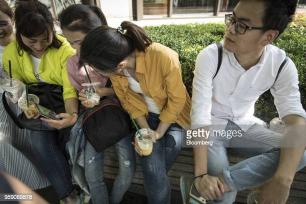 Customers sit with cups of iced beverages outside the Starbucks Corp Reserve Roastery store in Shanghai China on Friday May 11 2018 Starbucksis...