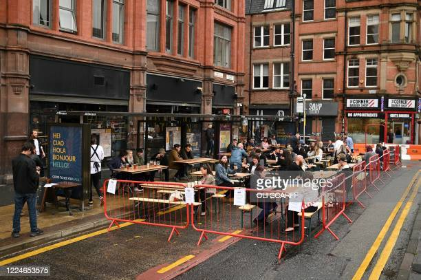 Customers sit with their drinks at tables in a road outside re-opened bars in Manchester, northwest England, on July 4, 2020 as the area embraces...