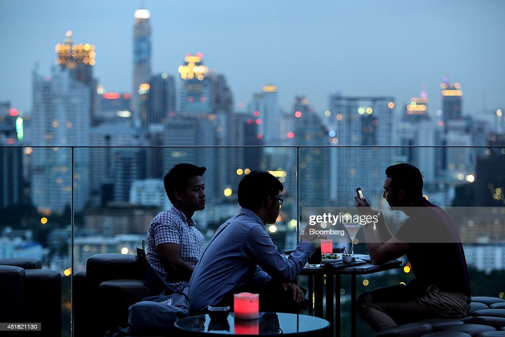 Customers sit with their drinks at the Park Society rooftop bar in the Sofitel So hotel, operated by Accor SA, at dusk in Bangkok, Thailand, on Saturday, June 28, 2014. Through a dozen coups, a tsunami, financial upheaval, floods and riots, Bangkok keeps bouncing back. With each crisis, tourism numbers slump, stocks crash and investment dips, only to return stronger than before. Photographer: Dario Pignatelli/Bloomberg via Getty Images