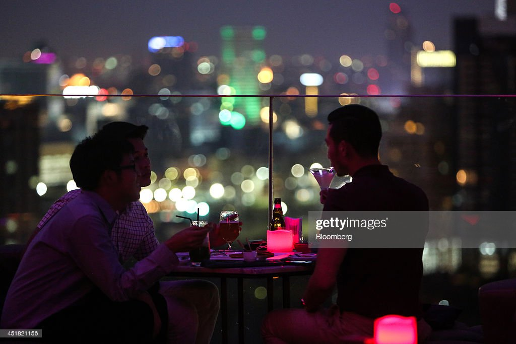 Customers sit with their drinks at the Park Society rooftop bar in the Sofitel So hotel, operated by Accor SA, at night in Bangkok, Thailand, on Saturday, June 28, 2014. Through a dozen coups, a tsunami, financial upheaval, floods and riots, Bangkok keeps bouncing back. With each crisis, tourism numbers slump, stocks crash and investment dips, only to return stronger than before. Photographer: Dario Pignatelli/Bloomberg via Getty Images