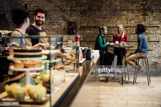 customers sitting in cafe with counter with food in foreground - coffee shop stock pictures, royalty-free photos & images