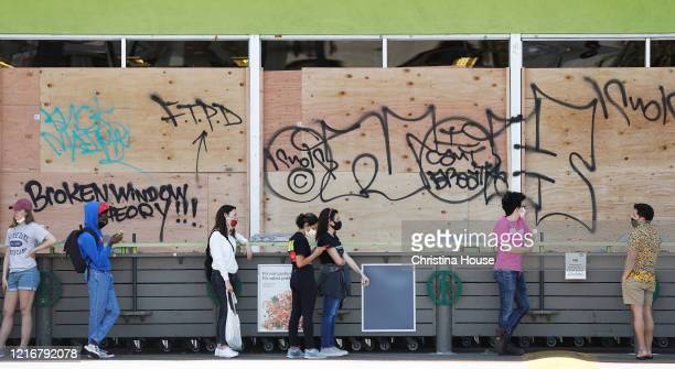 Customers social distance while waiting in line to shop at a boarded up Whole Foods on 3rd Street in the Fairfax District on Sunday May 31 2020
