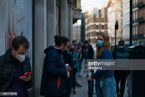 Customers socially distance as they queue for the new iPhone 12 and iPhone 12 Pro on launch day on October 23, 2020 in London, England. Apple's...
