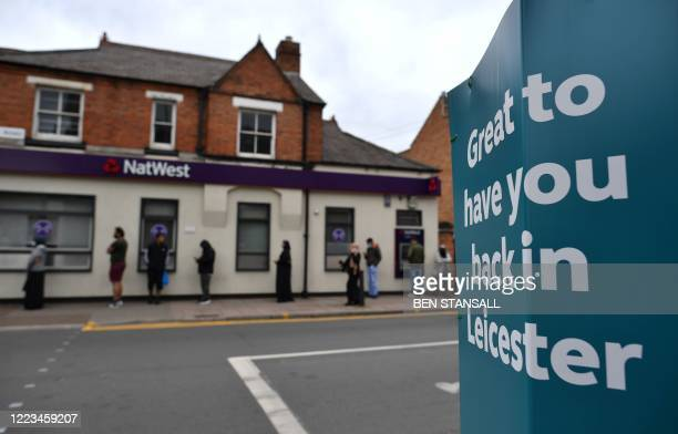 """Customers socially distance as they queue to enter a NatWest bank, opposite a sign reading """" Great to have you back in Leicester"""" in the North..."""