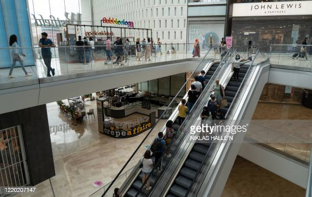 Customers some wearing face masks or coverings as a precaution against COVID19 walk past reopened shops inside the Westfield indoor shopping centre...