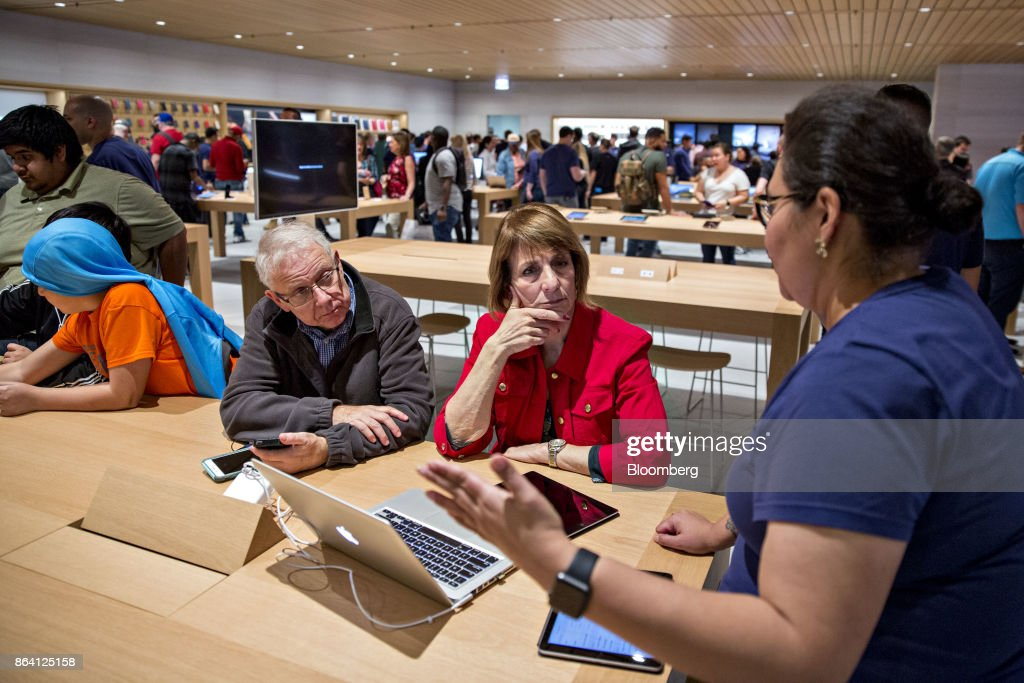 Customers speaks with an employee, right, during the opening of the new Apple Inc. Michigan Avenue store in Chicago, Illinois, U.S., on Friday, Oct. 20, 2017. The building features exterior walls made entirely of glass with four interior columns supporting a 111-by-98 foot carbon-fiber roof, designed to minimize the boundary between the city and the Chicago River. Photographer: Daniel Acker/Bloomberg via Getty Images