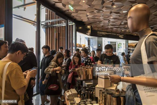 Customers stand around a merchandise stand inside the Starbucks Corp Reserve Roastery store in Shanghai China on Friday May 11 2018 Starbucksis...