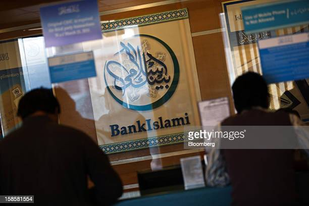 Customers stand at a counter in a BankIslami Pakistan Ltd bank branch in Karachi Pakistan on Tuesday Dec 18 2012 BankIslami the nation's...