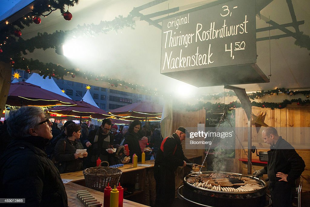 Customers stand at a stall as traders cook traditional German sausages at a market stall ahead of Christmas in Berlin, Germany, on Sunday, Dec. 1, 2013. Euro-area economic growth slowed to 0.1 percent in the third quarter after a 0.3 percent gain in the previous three months. Photographer: Krisztian Bocsi/Bloomberg via Getty Images