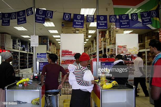 Customers stand at cash desks offering MPesa mobile phone money transfer services operated by Standard Bank Group Ltd at a supermarket in Tembisa...