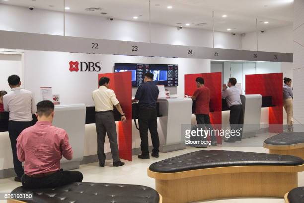 Customers stand at counters inside the DBS Group Holdings Ltd flagship bank branch in Singapore on Thursday Aug 3 2017 DBS Southeast Asia's largest...