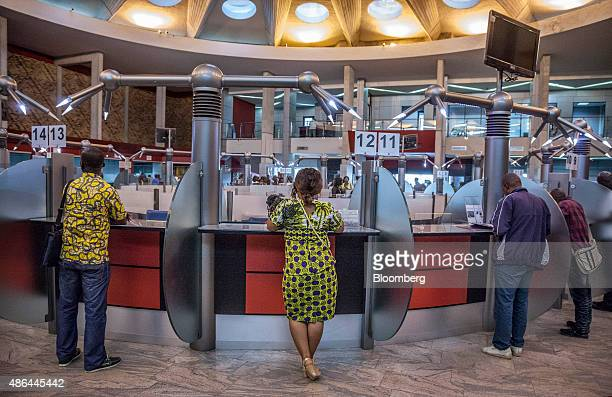 Customers stand at the service counters inside a Societe Generale de Banques en Cote D'Ivoire bank branch in Abidjan Ivory Coast on Monday Aug 31...