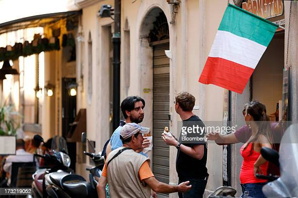 Customers stand beneath an Italian national flag as it flies above the entrance to a fast food restaurant in Rome Italy on Wednesday July 10 2013...