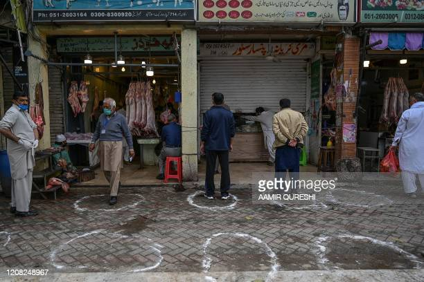 Customers stand in designated areas marked on the floor outside meat and grocery shops to maintain recommended social distancing during a...