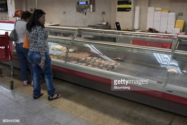 Customers stand in front of a counter displaying limited supplies of meat for sale at a grocery store in Caracas Venezuela on Tuesday Jan 9 2018...