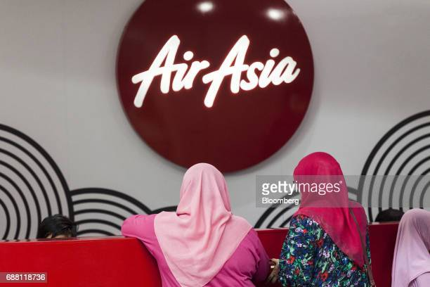 Customers stand in front of an AirAsia Bhd counter at Kuala Lumpur International Airport 2 in Sepang Selangor Malaysia on Thursday May 25 2017...