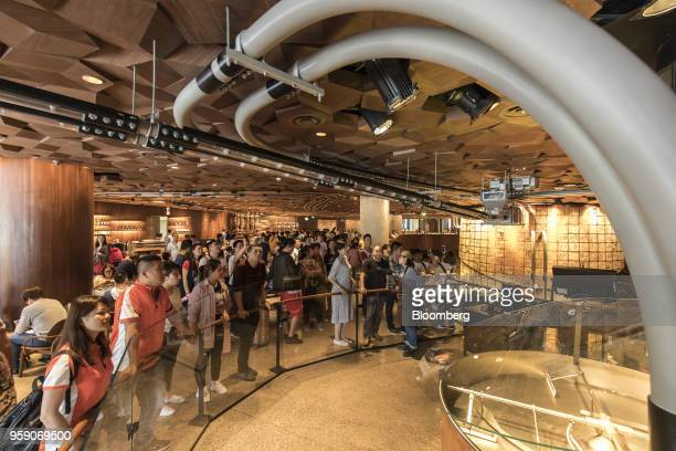 Customers stand in front of coffee beanprocessing equipment inside the Starbucks Corp Reserve Roastery store in Shanghai China on Friday May 11 2018...