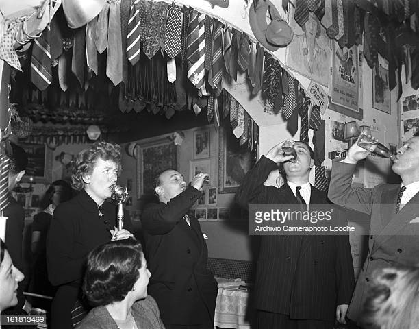 Customers stand in front of Lady Patachou while she is singing Paris 1950s