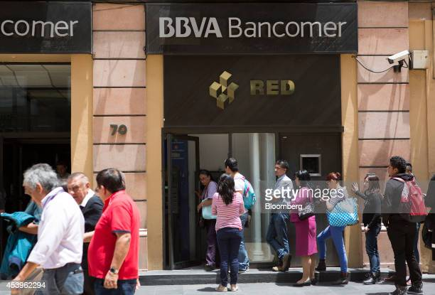 Customers stand in line at a BBVA Bancomer automated teller machine in Mexico City Mexico on Thursday Aug 21 2014 Mexican consumer prices rose more...